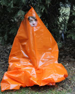 A young woman shows how a bright orange contractor bag with a hole cut out can become a life-saving temporary shelter from cold, wind and rain.