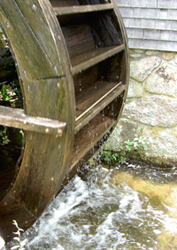 Picture of partial water wheel against stone wall with water below