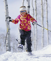 A girl in a red and yellow jacket snowshoeing