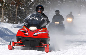 snowmobiles going along a trail