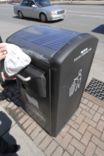Grey receptacle by side of street with solar panel on top and a hand opening it up to throw garbage away