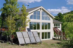 Ground mounted PV panel in front of house depicting small PV use