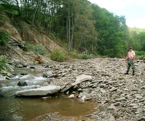 A man stands beside a heavily eroded stream and bank
