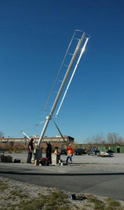 Single blade wind turbine against blue sky with men around base during installation