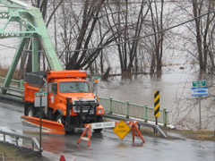 An orange truck parked on a bridge over a flooded river bank