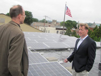 solar panel array on roof with two men: Mike Manning, Mayor and Jim Yenienger, Consultant