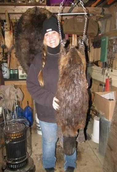 Laura Gidney poses for a picture with a large beaver fur.