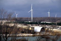 Four white wind turbines in a semi-forested landscape