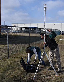 DEC staff set up a portable air monitoring instrument