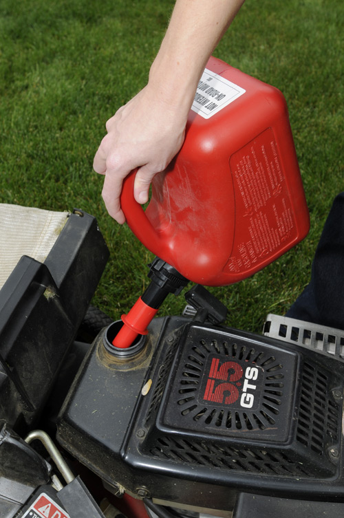A new gas can is being used to fill a lawn mower
