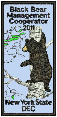 Patch sjowing a balck bear climbing a birch tree
