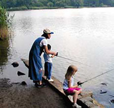 A mother and two children fishing on a lake