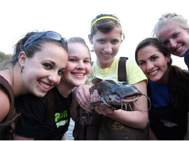 Marist College students display their 'catch of the day' during a field program at the Norrie Point Environmental Center. There are five young women in waders and one is holding a large catfish.