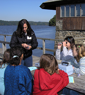 Middle school students investigate water quality in the Hudson River Estuary by performing chemical tests in the water. NYSDEC Educator leads the station. The students are working at a picnic table on the patio next to the river.