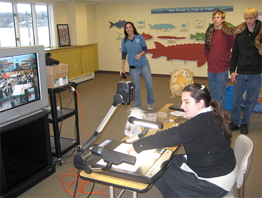 "SCA intern leading a distance learning program for a local middle school. Students from the Dutchess County Environmental Academy display a large snake in the background, and another educator is standing in front of the Reserve's ""fish wall"". The Hudson River is visible out the windows."