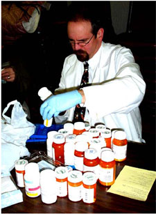 A pharmacist evaluating medications turned in at a household hazardous waste collection
