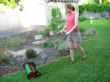 Woman mowing the lawn with a reel mower