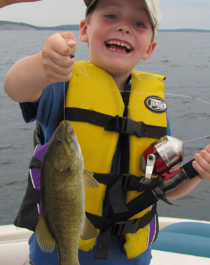 Image of a happy kid holding a smallmouth bass