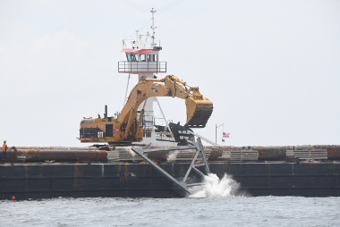 Construction material being deployed from a barge to provide additional structure to Shinnecock Reef