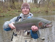 Angler with colorful male steelhead caught on Canadaway Creek