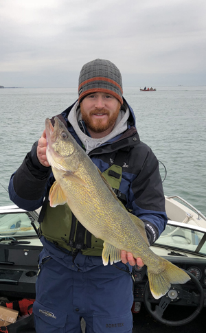 man holding up walleye from Lake Erie