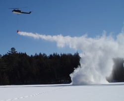 a helicopter spreading lime on an ice covered pond.