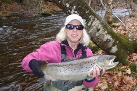 a woman holding a large brown trout