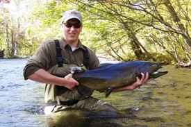 Angler with large male chinook salmon