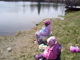 Photo of two young girls fishing on pond bank