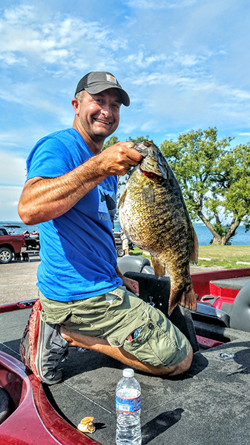Patric Hildebrand with the 8 lb. 4oz. state record holder smallmouth bass he caught.