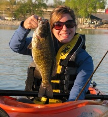 Woman angler in kayak holding smallmouth bass.