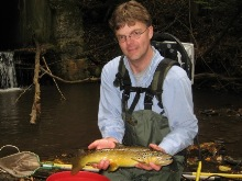 Technician holding large wild brown trout collected during survey.