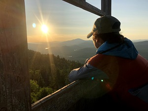 a woman in a fire tower looking out at a sunset