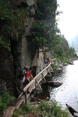 backpackers carry their tents and gear walking on a narrow path between the side of a hill and water's edge