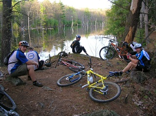 group on mountain bikiers resting by a pond