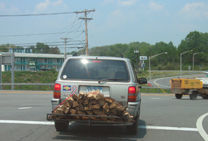 Van with firewood strapped to the back driving on road