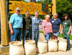 A group of student craftspeople stand behind their newly created traditional Adirondack packbaskets