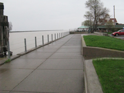 Wide concrete walkway with cable railing overlooking Genesee River