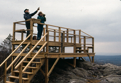 Two people standing on the viewing platform at Hawk Watch Trailway