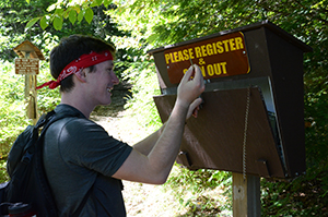 hiker registering at the trailhead sign in
