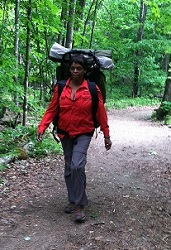 woman hiking in the woods wearing a backpack