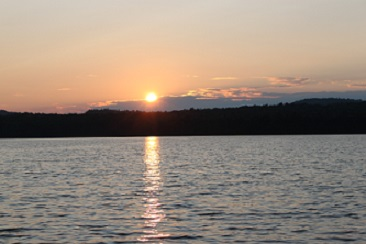 Sunset on Little Tupper Lake with the sun reflecting on the rippling water