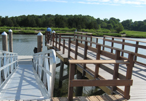Wooden fishing pier and metal gangway to floating dock at low tide