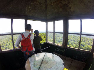 Two people inside the Hunter Mountain Fire Tower