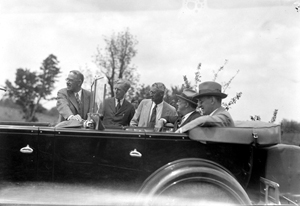 FDR meets with officials while seated in a convertible car