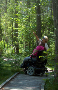 A wheelchair and its occupant on an accessible trail