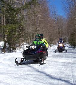 A pair of snowmobiles on a trail