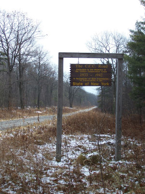 """The CCC Road"" sign in light snow and tall grass."