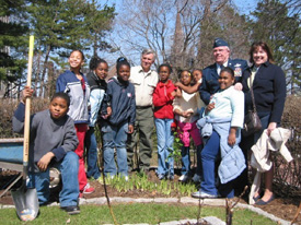 photo of Arbor Day ceremony - a group of children and three adults planting trees