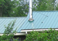 Metal roof on home near woods
